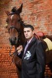 Marié pendant la promenade contre un cheval brun et un vieux mur de briques Images stock