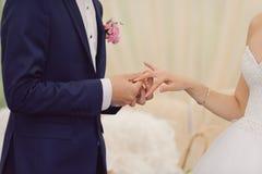 Marié Putting sur l'anneau sur le doigt de la jeune mariée photos stock