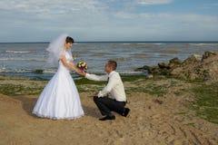Marié se mettant à genoux avant la jeune mariée Images stock