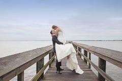 Marié supportant sa jeune mariée Images libres de droits