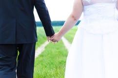 Marié tenant la jeune mariée Photographie stock libre de droits