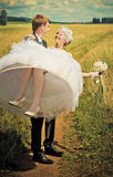Marié tenant sa jeune mariée Photo libre de droits
