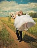 Marié tenant sa jeune mariée Photos libres de droits