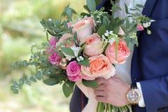 Marié tenant un beau bouquet nuptiale Bouquet de mariage des roses de pêche par David Austin, aqua tête simple de rose de rose, e Images stock