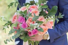 Marié tenant un beau bouquet nuptiale Bouquet de mariage des roses de pêche par David Austin, aqua tête simple de rose de rose, e Photographie stock