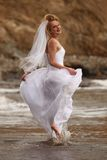 Mariée assez blonde le long de l'océan Photographie stock libre de droits