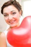 Mariée avec le ballon en forme de coeur rouge Image stock
