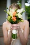 Mariée avec le bouquet devant son visage Image stock