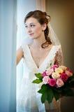 Mariée avec le bouquet près de l'hublot Photo stock
