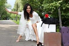Mariée d'emballement faisant de l'auto-stop Image libre de droits