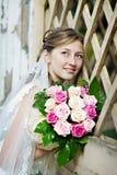 Mariée dans la robe blanche avec des fleurs Image stock