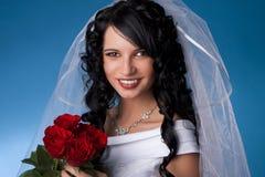 Mariée de Brunette avec les roses rouges Photographie stock libre de droits