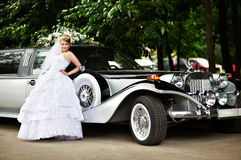 Mariée de luxe dans la robe de mariage au sujet de la limousine Photo stock