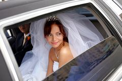 Mariée de sourire avec le marié dans la limousine de mariage photo libre de droits