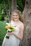 Mariée de sourire contre un arbre Photos stock
