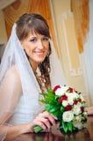 Mariée de sourire dans la robe blanche avec le bouquet des roses Photographie stock libre de droits