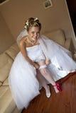 Mariée de sourire plaçant la jarretière Images stock