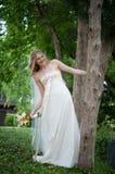 Mariée de sourire se penchant à l'extérieur d'un arbre Photographie stock libre de droits