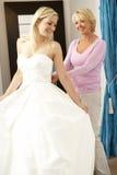 Mariée essayant sur la robe de mariage avec des ventes auxiliaires Photo libre de droits