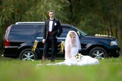 Mariée et marié à côté de véhicule de mariage Photos libres de droits