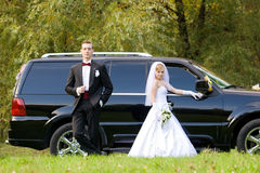 Mariée et marié à côté de véhicule de mariage Photo libre de droits