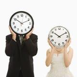 Mariée et marié avec des horloges. image stock