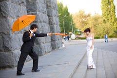 Mariée et marié avec les parapluies oranges Photo stock