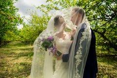 Mariée et marié dans des baisers de stationnement Photographie stock libre de droits