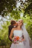 Mariée et marié dans des baisers de stationnement les jeunes mariés de nouveaux mariés de couples à un mariage dans la forêt de v Image stock