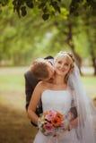 Mariée et marié dans des baisers de stationnement les jeunes mariés de nouveaux mariés de couples à un mariage dans la forêt de v Photographie stock
