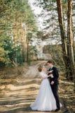 Mariée et marié dans des baisers de stationnement les jeunes mariés de nouveaux mariés de couples à un mariage dans la forêt de v Images stock