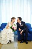 Mariée et marié dans un fauteuil bleu Photographie stock libre de droits