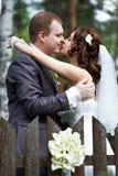 Mariée et marié de baiser au sujet de frontière de sécurité en bois Image stock