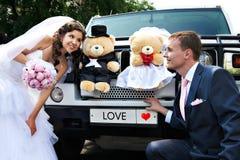 Mariée et marié heureux au sujet de limousine de mariage Images stock