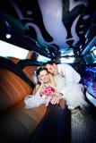 Mariée et marié heureux dans la limousine de mariage Photographie stock libre de droits