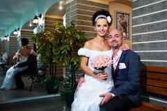 Mariée et marié heureux sur le banc dans l'intérieur moderne Photographie stock libre de droits