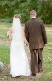 Mariée et marié marchant le long d'un chemin image libre de droits