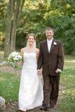 Mariée et marié marchant le long d'un chemin images stock