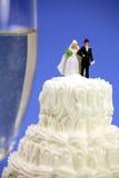 Mariée et marié miniatures sur le gâteau de mariage Images stock