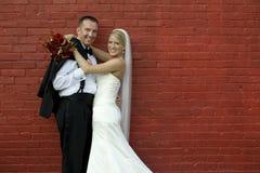 Mariée et marié par le mur de briques Image stock