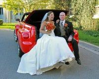 Mariée et marié posant dans le camion rouge convertible Photographie stock