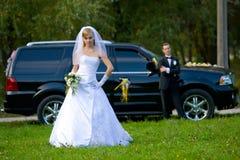 Mariée et marié restant devant le véhicule de mariage Image libre de droits