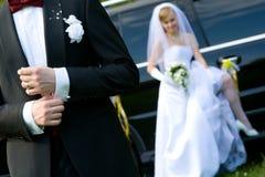 Mariée et marié sur le fond de véhicule de mariage Images libres de droits