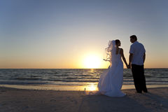 Mariée et mariage de plage par marié de coucher du soleil de ménages mariés