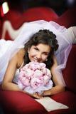 Mariée heureuse avec le bouquet de mariage dans la limousine photos stock