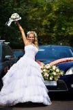 Mariée heureuse avec le bouquet près du véhicule de mariage Photographie stock libre de droits