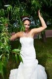 Mariée heureuse dans la robe de mariage et le branchement de l'arbre Image libre de droits