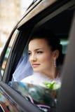 Mariée heureuse dans un véhicule de mariage Images stock