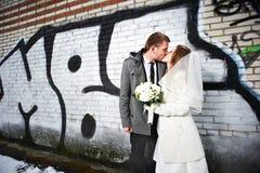 Mariée heureuse et marié embrassant près du graffiti Photos libres de droits