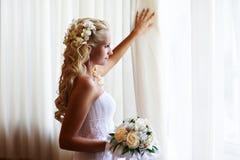 Mariée heureuse près d'hublot avec des fleurs images libres de droits